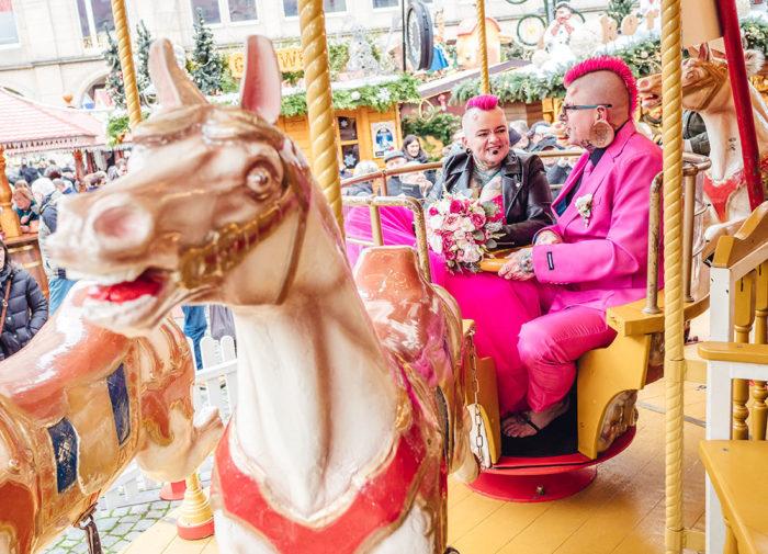 Hochzeitsfotos Dresden Striezelmarkt Brautpaar in pink auf Karussell
